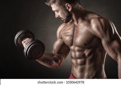 Handsome muscular man doing sport with dumbbell on dark background