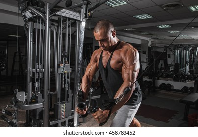 Handsome muscular man exercise with cable in gym.
