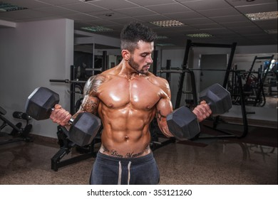 Handsome muscular man exercise with weights in the gym.