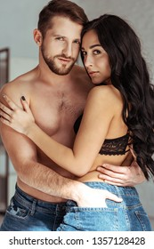 handsome and muscular man hugging beautiful woman in bra and looking at camera
