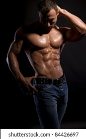 Handsome, muscular man in jeans  with water-drops