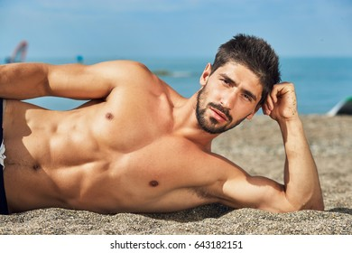 Handsome muscular man lying on beach. Sea background.
