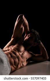 Handsome muscular man lying and posing on bench