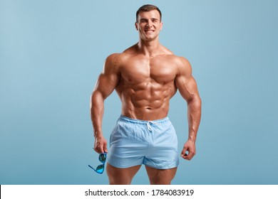 Handsome muscular man naked torso abs, isolated on blue background. Fitness male model with fashionable sunglasses