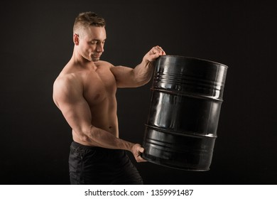 handsome muscular man on a black background holding an iron barrel