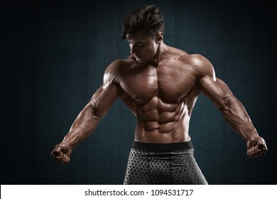 Handsome muscular man on wall background, shaped abdominal. Strong male naked torso abs