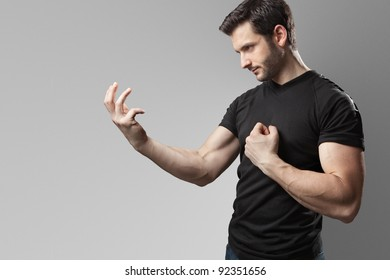 A handsome muscular man posing in the act of a oath wearing a black t-shirt and a pair of jeans