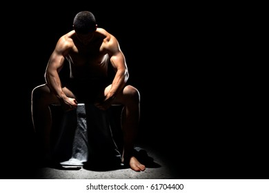 A handsome muscular man posing on a black background sitting down and resting with his head bowed