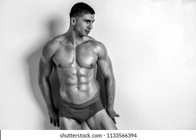 Handsome muscular man posing in underwear on white background
