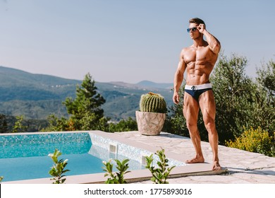 Handsome muscular man relaxing in swimming pool outdoors on summer day.  Attractive rich male posing with abs and muscles on his luxury villa swimming pool