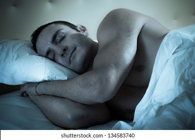 an handsome and muscular man sleeping peacefully in a bed