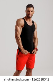 Handsome muscular man in sport clothes posing on gray background