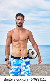 Handsome muscular man stands on the beach with football ball