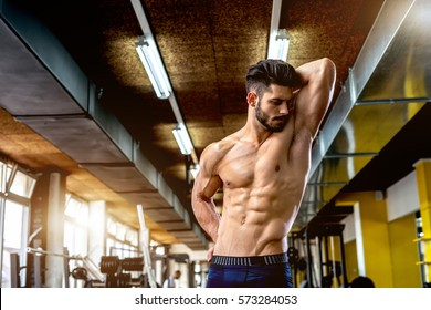 Handsome muscular man stretching at gym.