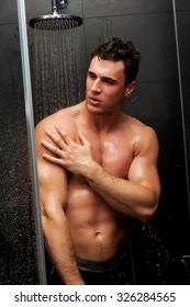 Handsome muscular man taking the shower.