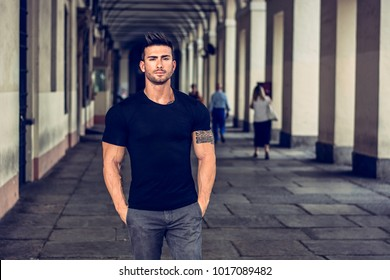 Handsome muscular man with tattoo posing in European city center, Turin, Italy, outside under colonnade