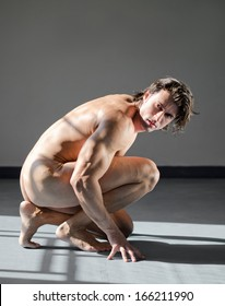 Handsome, muscular man totally naked, kneeling on the floor in studio shot