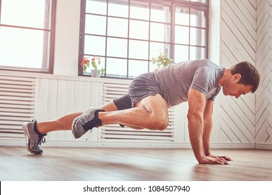 Handsome muscular man in a t-shirt and shorts doing functional exercises on floor at home.