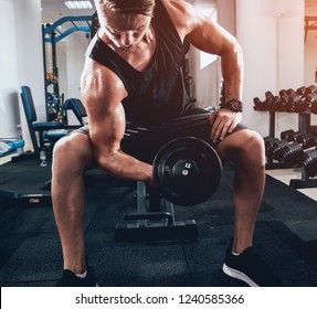 Handsome muscular man working out with dumbbells. Fitness concept.