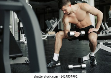 Handsome muscular man working out with dumbbells in the gym.
