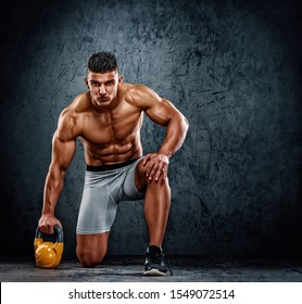 Handsome Muscular Men Exercise With Kettlebell. Cross training athlete