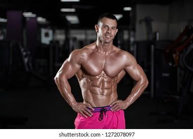 Handsome muscular sexy man posing in gym. Tanned athlete.