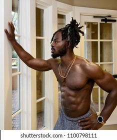 Handsome muscular shirtless African American man looking through the window.