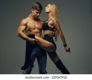 Handsome muscular shirtless guy holding long leg of his sexy blond young woman. Isolated on grey background.