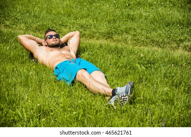 Handsome Muscular Shirtless Hunk Man Outdoor in City Park Laying on the Grass. Showing Healthy Muscle Body While Looking away