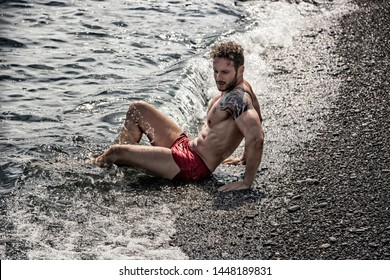 Handsome muscular shirtless man on the beach lying on gravel, with eyes closed