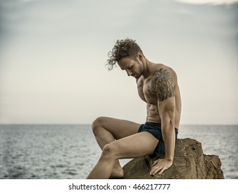 Handsome muscular shirtless man on the beach sitting on rocks, looking at camera