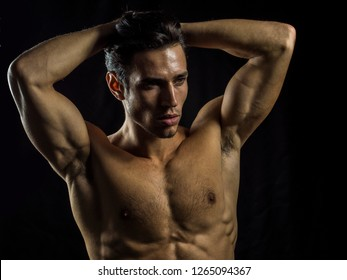 Handsome muscular shirtless young man standing confident, front view, looking away