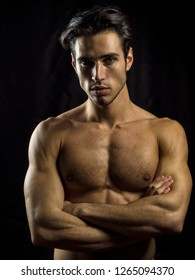 Handsome muscular shirtless young man standing confident, front view, looking at camera