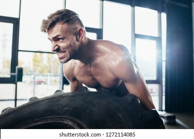 handsome muscular sportsman lifting tire and grimacing in gym