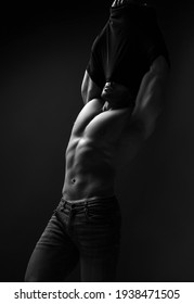 Handsome muscular strong man in jeans, weightlifter with perfect built body is taking off his shirt, getting naked, demonstrating perfect abs and chest muscles over dark background. Black and white
