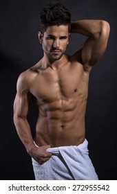 handsome muscular young bodybuilder showing his muscles and abs while posing shirtless