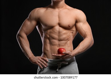 Handsome muscular young man with apple on black background