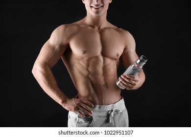 Handsome muscular young man with bottle of water on black background