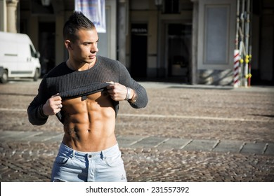 Handsome muscular young man outdoor in city lifting shirt to show abs