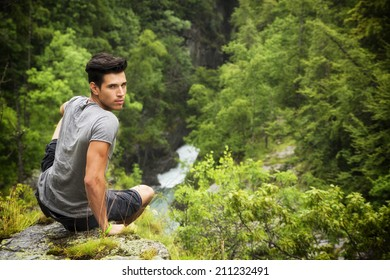 Handsome muscular young man sitting in lush green mountain scenery looking at camera