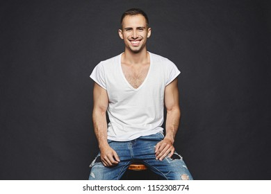A handsome muscular young men with beard, in white t-shirt and in fashionable jeans sits on a chair, smiles and posing at black background