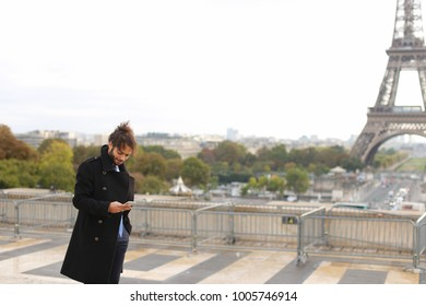Handsome Muslim boy talking on smartphone with French fiancee close to Eiffel Tower in slow motion. Handsome man has black curly hair, beard and straight nose, dressed in black coat. Concept of modern