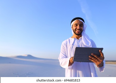 Handsome Muslim businessman with tablet solves important work issues and problems, smiles and moves finger along touch screen of gadget, standing on white clean sand in desert outdoors on warm summer