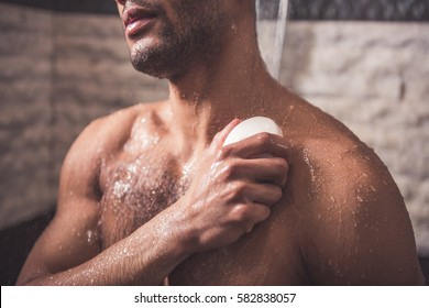 Handsome naked Afro American man is using a soap while taking shower in bathroom
