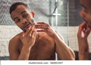 Handsome naked Afro American man is squeezing pimples on his face while looking into the mirror in bathroom