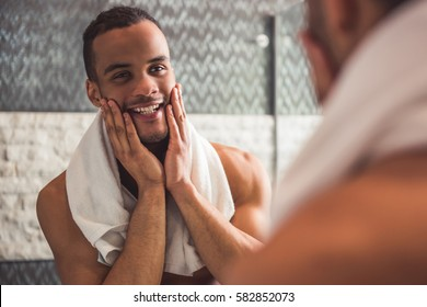 Handsome naked Afro American man is touching his face and smiling while looking into the mirror in bathroom