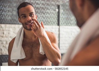 Handsome naked Afro American man is applying cream on his face and smiling while looking into the mirror in bathroom