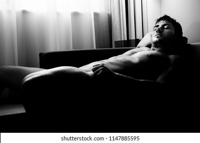 Handsome naked man with abs, muscular, hunky body lying on sofa