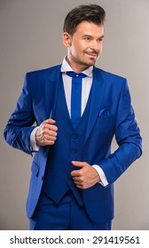 Handsome nifty man in stylish blue suit and tie posing at studio.