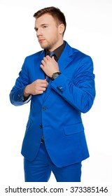Handsome nifty man in stylish blue suit  tying the necktie - isolated on white background.